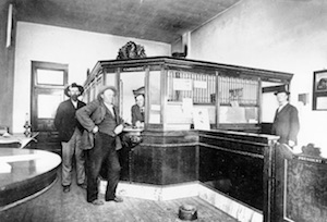 Historic bank interior layout with patrons standing at counter