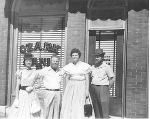 Men and women standing outside of original Ozark Bank location